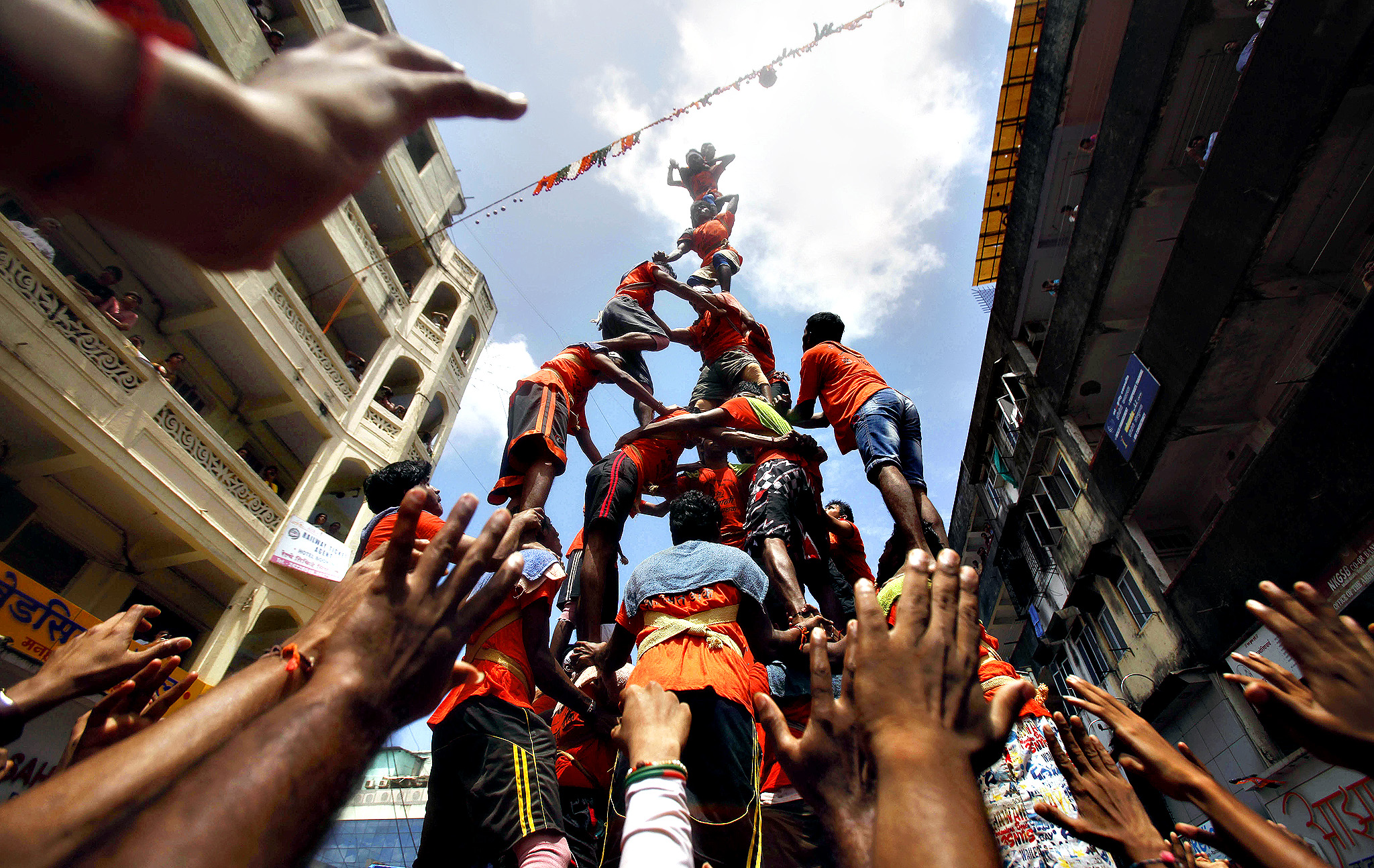 "Devotees build a pyramid in an attempt to break the ""Dahi handi,"