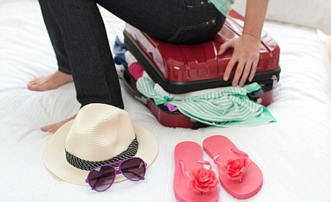 Close-up of a woman trying to close her suitcase